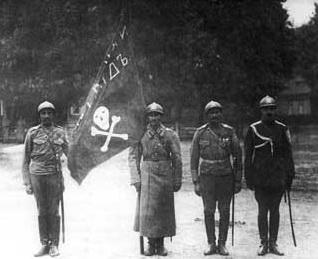 Знаменщик, ассистенты и адъютант ударного полка поручик князь Ухтомский, 1917 г.. На касках — череп со скрещенными костями.